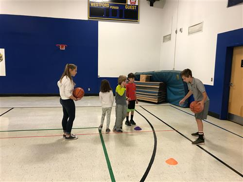 AWOD students teaching dribbling skills to ms Richardson's class