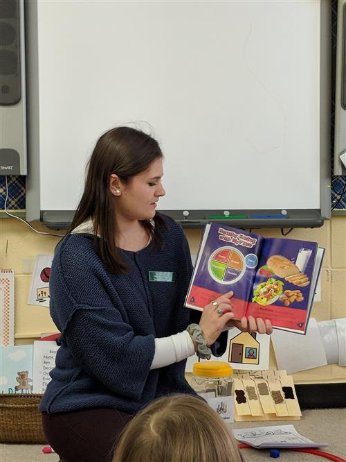 Student Nurse Sally reading a book to students