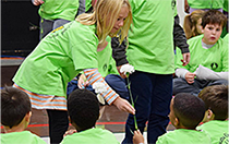 Third-grade buddy hands flower to kindergartner