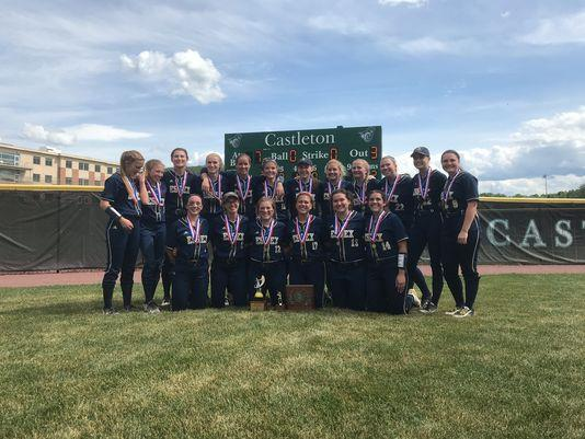 Girls softball team posing with championship trophy