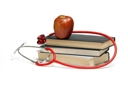 Stack of three books with an apple and stethoscope on top