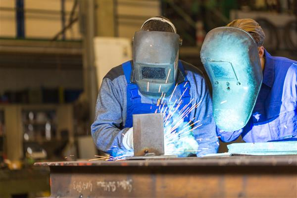 Two people welding.