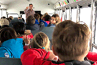 Students practice safely evacuating a school bus