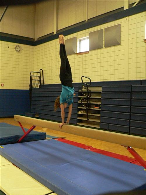 girl doing handstand on the balance beam