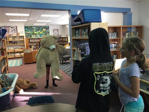 using an iPad, students work to film a student moving a large bear.