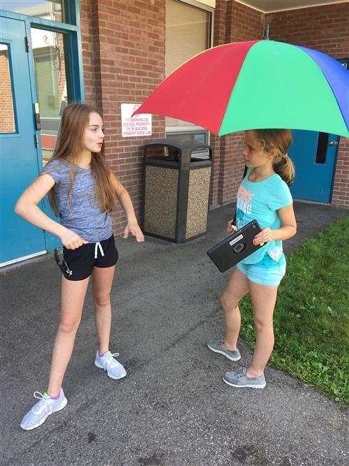 Students plan their filming outside using an umbrella as a prop.