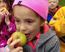 girl with pink hat eating apple